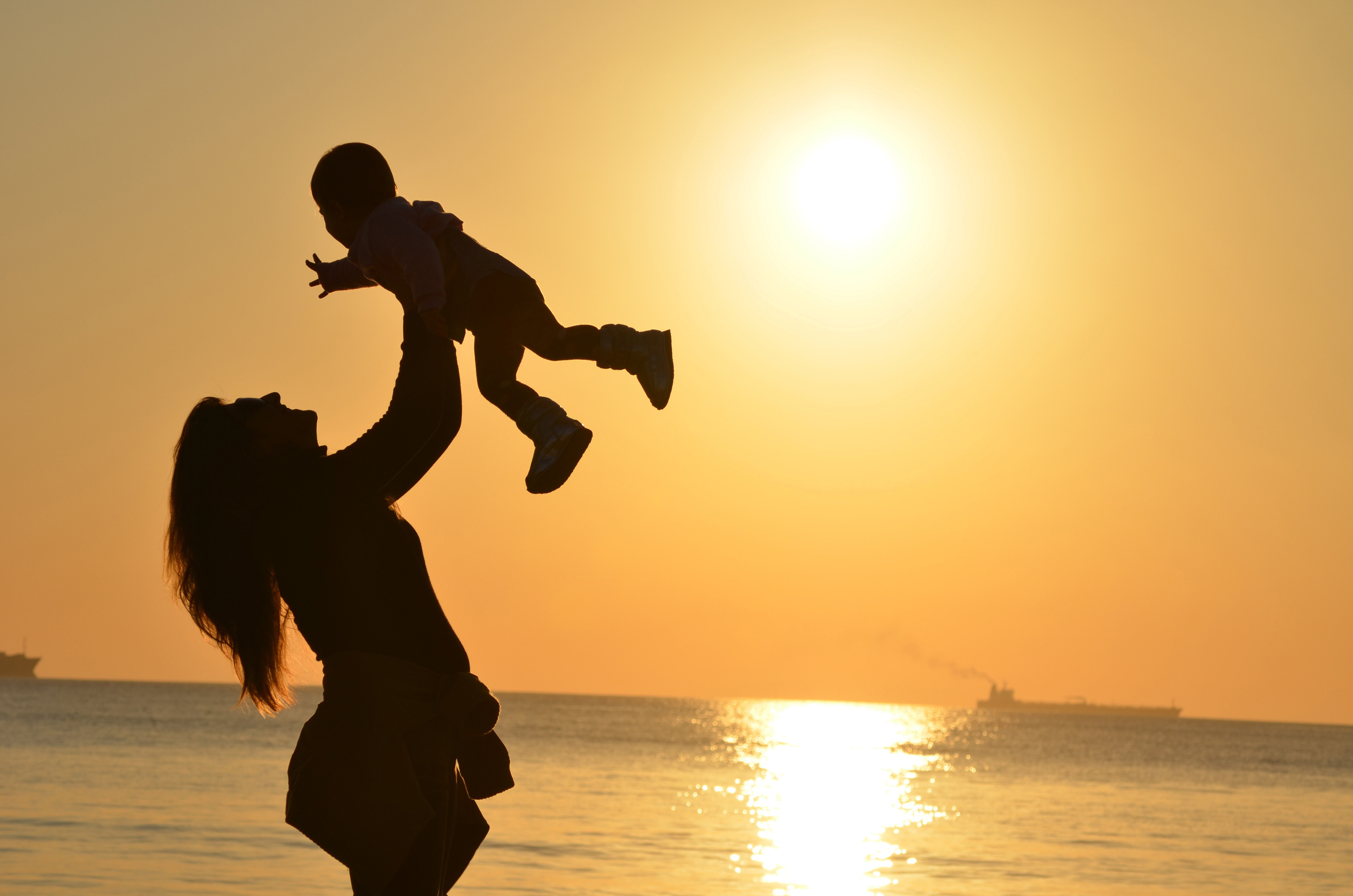 Mother Carrying Baby sunset